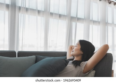 Happy lifestyle asian woman relax and sleep on sofa in living room at home