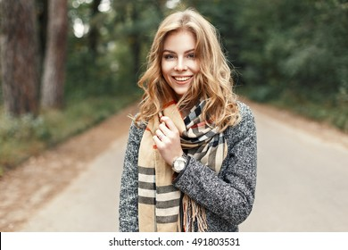 Happy Lifestyle portrait of a beautiful young model girl with a sweet smile in a warm autumn scarf.