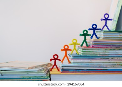 A happy line of rainbow pipe-cleaner people going up the ladder of success through reading and education. A lovely photo for international or multicultural ideas and concepts for adults and children.