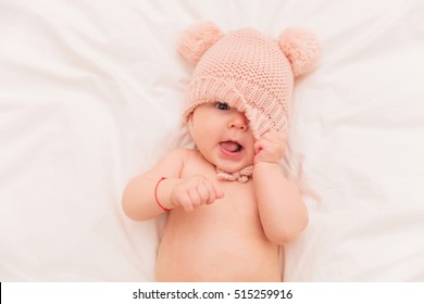 happy litthe baby girl covering one eye with her hat while lying on her bed
