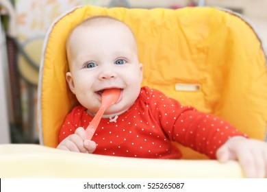 Happy little 6 months baby girl with spoon