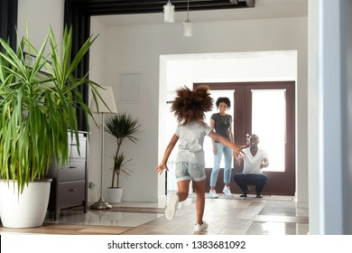 Happy little African American girl run to dad excited to meet him after work, funny small child rush to black young father return home after business trip, daddy wait to hug child in hallway
