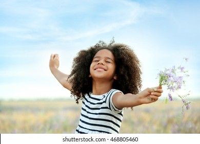 Happy little African American girl in the field