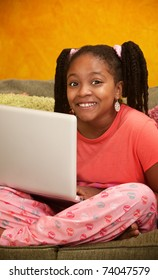Happy little African American girl using a laptop