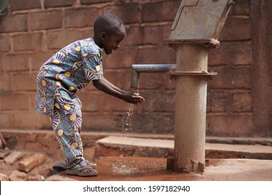 Happy Little African Boy Washing His Hands At the Village Pump