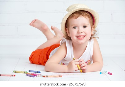 happy little artist  girl in a hat draws pencil lying on the floor