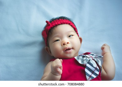 Happy Little asian baby is smiling on the blue bed , she wear red dress with a bow and red Headband