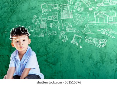 Happy little asian boy kid in hard hat doodle chalk drawing with sketching of building icon construction on school green chalkboard background