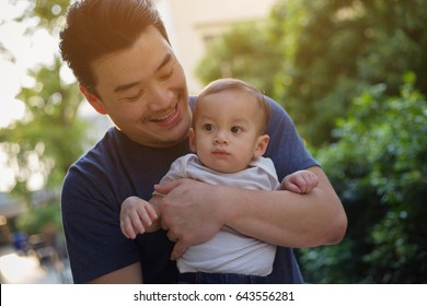 Happy little Asian boy playing with his father