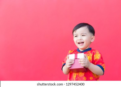 Happy Little asian boy wear Chinese traditional shirt smiling with holding gift box and envelope. Happy chinese new year concept.