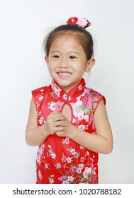 Happy little Asian child girl wearing red cheongsam with greeting gesture celebration for Chinese New Year isolated on white background.