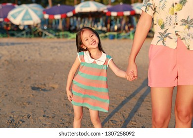 Happy little Asian child girl holding mother hands together on beach while evening sunlight.