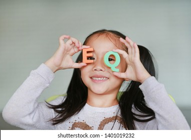 Happy little Asian child girl holding alphabet EQ (Emotional Quotient) text on her face. Education concept.