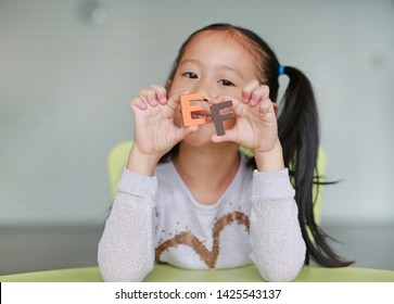 Happy little Asian child girl holding alphabet EF (Executive Functions) text on her face. Education and development concept.