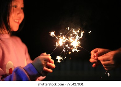Happy little Asian child girl enjoy playing firecrackers.