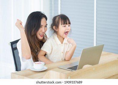 Happy little Asian daughter and mother look at the computer laptop together, have a cheerful expression in house on holiday