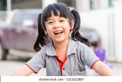 Happy Little asian girl child showing front teeth with big smile and laughing : Healthy happy funny smiling face young adorable lovely female kid.Joyful portrait of asian elementary school student.
