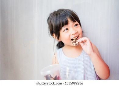 Happy Little asian girl child eating Crispy brownie with almond and showing front teeth with big smile and laughing she have delicious.Healthy happy funny smiling face Adorable lovely female kid.