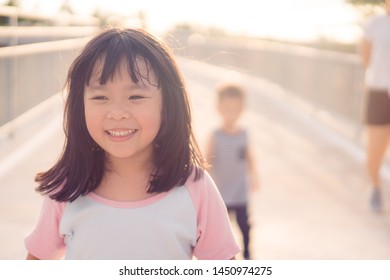 Happy Little asian girl child showing front teeth with big smile and laughing: Healthy happy funny smiling face young adorable lovely female kid.Joyful portrait of asian girl walking in playground.