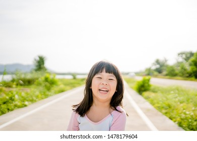 Happy Little asian girl child showing front teeth with big smile, laughing and jogging in summer park in Japan : Healthy happy funny smiling face young adorable lovely female kid.Joyful portrait girl.