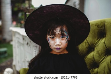 Happy little Asian girl child with black witch costume sitting outdoor on couch. Fall activity. Rustic country living in autumn. Purple hat with belt. Face painting.Lipstick and boots.