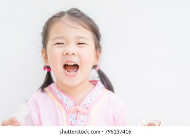 Happy Little asian girl in chinese traditional dress smiling and eating chocolate egg .Happy chinese new year concept.