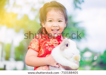 9c649ec24aa Happy Little asian girl in chinese traditional dress smiling and holding  big rabbit and showing front