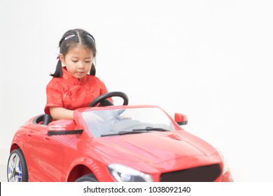 Happy little asian girl drive toy car.4 years old girl in chinese dress in a red toy car on the street.Little asian girl driving big toy car and having fun, outdoors.save drive and travel concept.