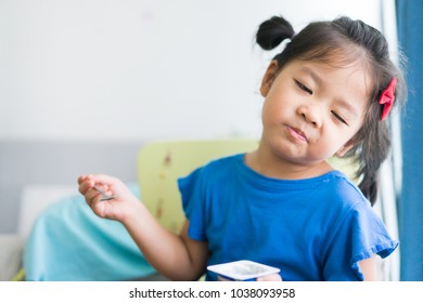 Happy Little asian girl eating yogurt and she have spoon in her mouth and Bad taste face of yogurt.Little girl face bad taste concept.