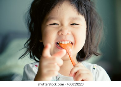 Happy Little asian girl eating yogurt and she have spoon in her mouth.
