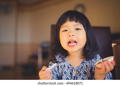 Happy Little asian girl eating chocolate and she have spoon in her mouth.