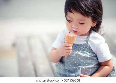 Happy Little asian girl eating soft cream or ice cream and she sit on the wooden table outdoor.Hokkaido Japan.