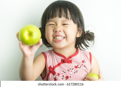 Happy Little asian girl eating green apples.Little asian girl wear chinese traditional dress.