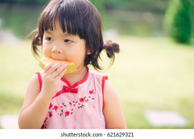 Happy Little asian girl eating delicious juicy honeydew melon from Japan.Little asian girl wear chinese traditional dress.