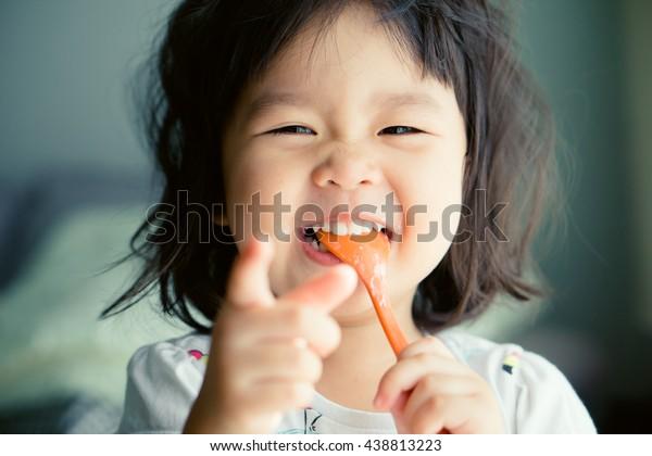 Heureuse petite fille asiatique mangeant du yaourt et elle a une cuillère dans la bouche.