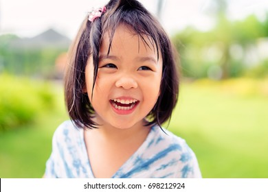 Happy little asian girl having fun at the park.Little asian girl child showing front teeth with big smile.Healthy happy funny smiling face child.Joyful portrait of asian elementary school student.