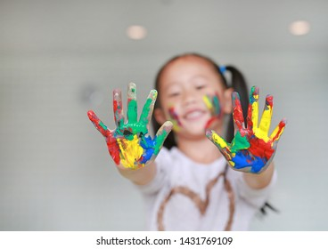 Happy little Asian girl with her colorful hands and cheek painted in the children room. Focus at baby hands.