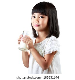 Happy little Asian girl holding a cup of milk, isolated over white.