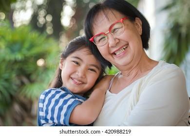 Happy little Asian girl hugging her grandmother