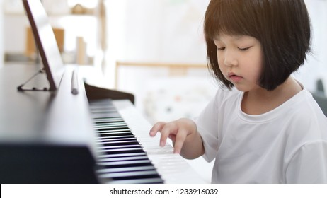 Happy little Asian girl playing piano