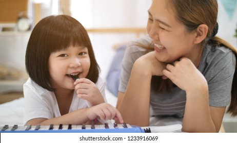 Happy little Asian girl playing melodica blow organ with mother