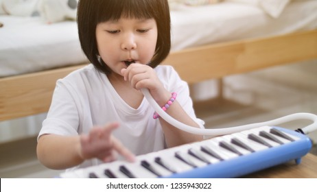 Happy little Asian girl playing melodica blow organ