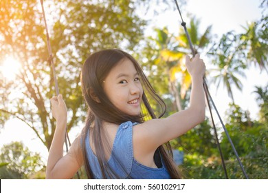 Happy little Asian girl playing swing outdoor in the park
