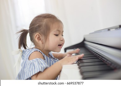 Happy little Asian girl playing piano at home