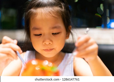 Happy Little asian girl ready to eat kakigori bingsu strawberry cheese cake and she have spoon in her hands.