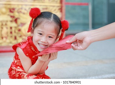 Happy little Asian girl received a red envelope. Chinese New Year celebration.