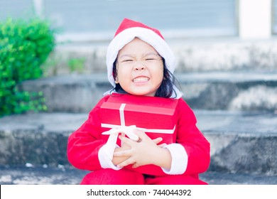Happy Little asian girl smile and holding red gift box in Christmas day.child holding gift box and surprise face.
