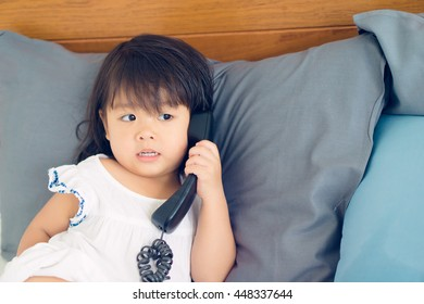 Happy little asian girl talking on phone on her bed.