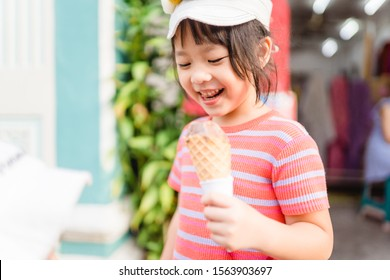 Happy Little asian girl walking and enjoy eating chocolate soft cream cone or ice cream cone at street in summer season.Street food and dessert in Phuket sunday walking street Thailand.