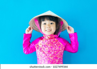 Happy little asian girl wearing Vietnamese hat in pink Ao dai Vietnam Traditional dress on blue background.Dress culture Vietnamese concept.